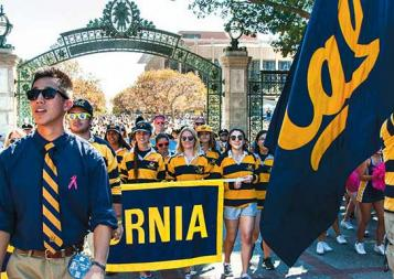 UC Berkeley students holding Cal floag and banner in a parade