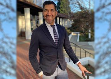 College Admissions and Career Planning certificate program instructor Armando Diaz in blazer and tie, standing next to railing with pillars in background. Photo.