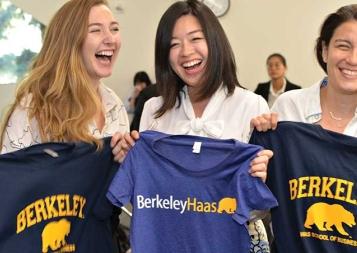 Three female students holding Berkeley and Berkeley Haas tshirts