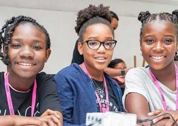 Image of three young black girls smiling at the camera