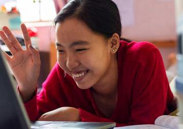 Asian female college student waving to laptop screen