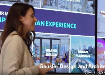 Student standing in front of a video wall showing Gensler services