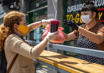 Two women wearing face masks at a curb-side pickup restaurant