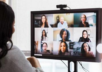 Photo of black young professional collaborating with team through online conferencing