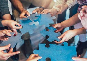 Photo of hands holding pieces of a jigsaw puzzle