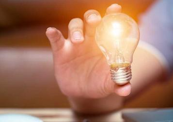 image of hand holding a lightbulb