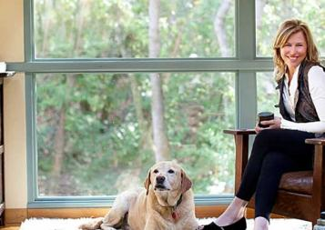 Photo of Llisa Staprans sitting on a leather chair with dog at her feet