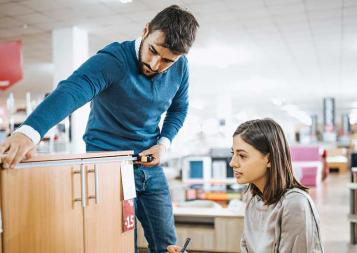 Photo of a couple shopping for school furniture