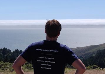 BHGAP student Hugo wears his Haas School of Business t-shirt and looks out over a view of Berkeley