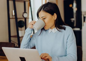 Stock photo of woman working from home and drinking coffee