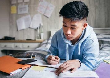 Photo of student lying on bed doing homework