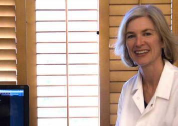 Photo of Jennifer Doudna next to a computer screen showing genome