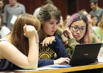 Three female students in a Berkeley classroom looking at a laptop