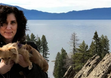 Marianna Lenoci posing in front of a Sierra lake while holding her puppy