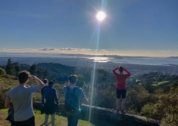 BHGAP student Markus and a few friends looking at a beautiful view of mountains and the ocean during a hike