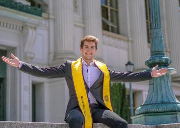 Markus sits atop a ledge in front of Doe Library wearing a suit and the Berkeley graduation stole, smiling with his arms outstretched