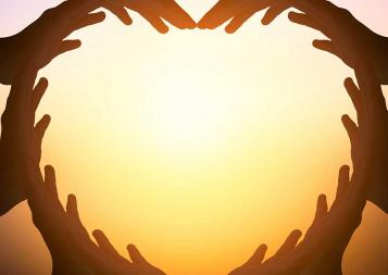 Illustration of hands joined together to shape a heart with sun in background