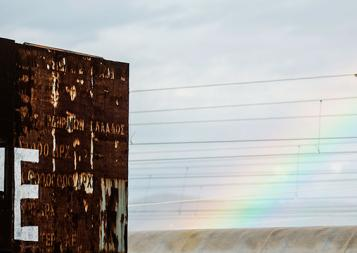 """Stock photo of Greek refugee center with """"hope"""" graffiti and rainbow"""
