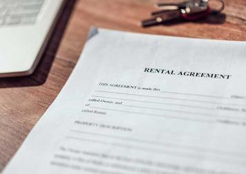 Photo of rental agreement paperwork next to a laptop
