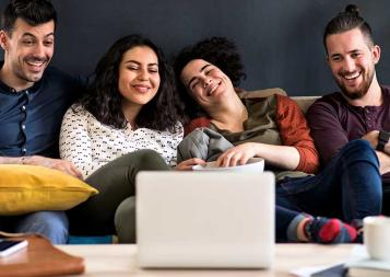 four friends laughing on a couch while watching something on a laptop