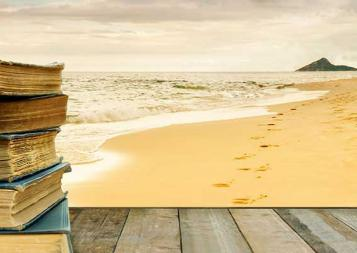 Stack of books on a wood platform on a beach