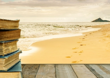 stock photo of a stack of books on a woden table by the beach