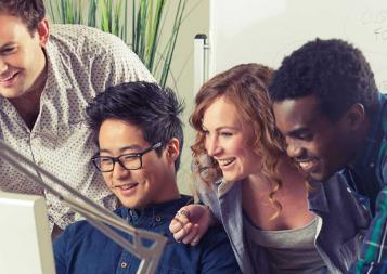 Photo of four diverse young professionals looking at a computer screen