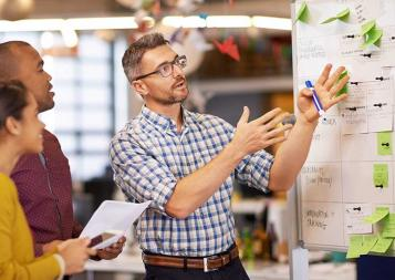 Man pointing at whiteboard with sticky notes while 2 colleagues look on