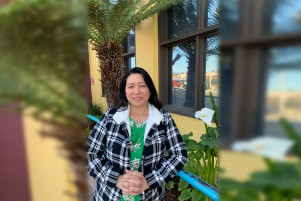 Carmel Gacho in plaid jacket in front of a tree and yellow building