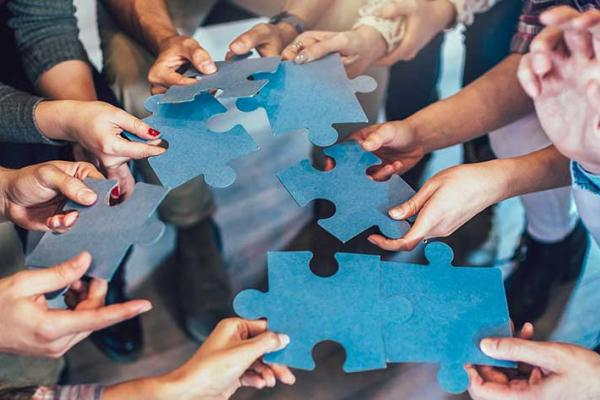 Group of diverse professionals holding jigsaw puzzle pieces