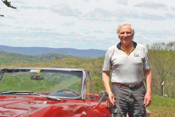 Writing certificate graduate and author Bill Truran next to a red sports car with hills behind him. Photo.