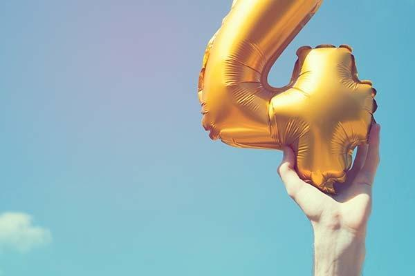 Image of hand holding a number 4 balloon against a blue sky