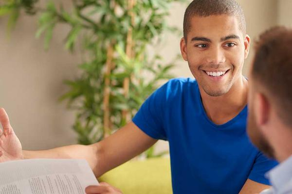 College admissions counselor and high school student work on essay writing