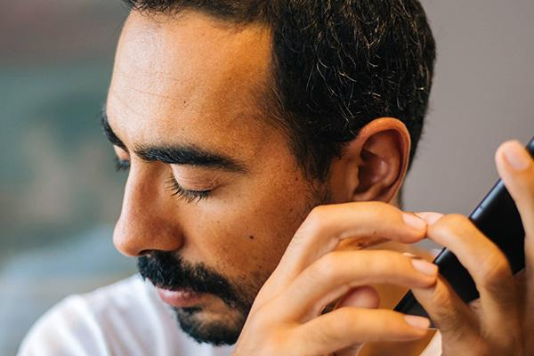 Photo of man eyes closed, turned away from cell phone, listening with left ear