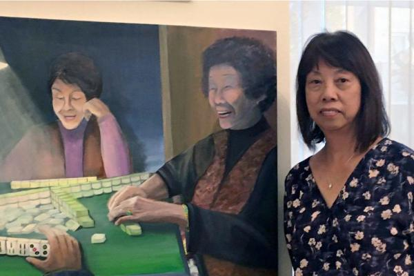 Certificate graduate Elinor Cheung in front of her painting depicting laughing Chinese women enjoying a game of mah-jongg