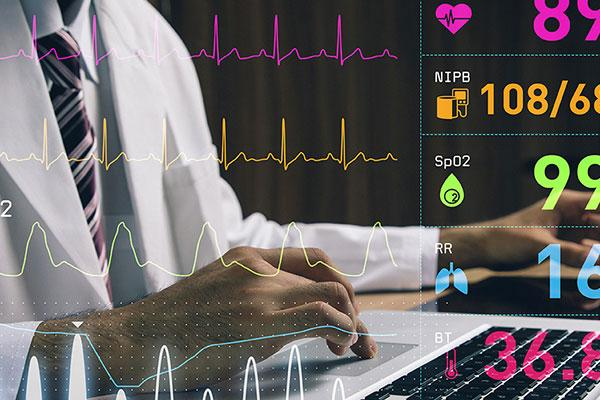Chest-view stock photo of a male medical professional working on a laptop with medical records overlayed on shot