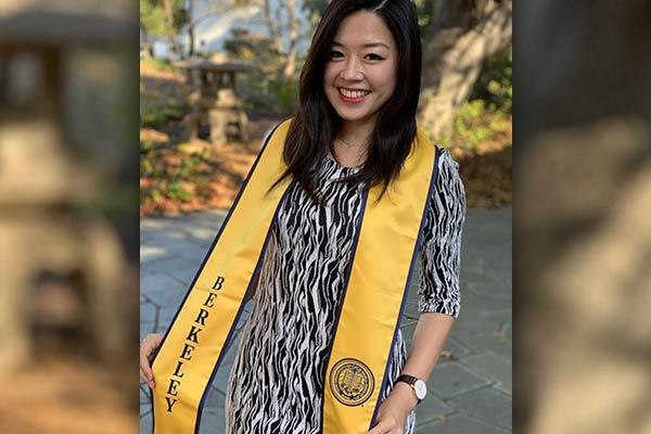 Jolin Wu wearing a Berkeley graduation scarf standing in front of some trees