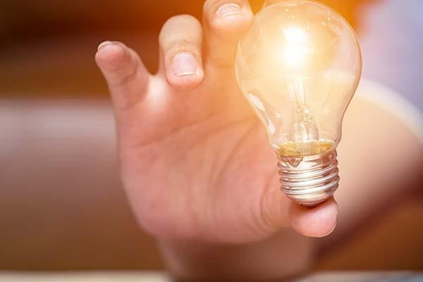 man holding lightbulb in foreground