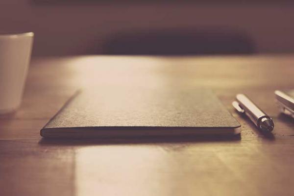 Image of closed notebook and pen on wooden table