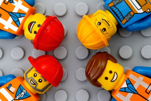 Still from lego movie with builders lying on a lego background