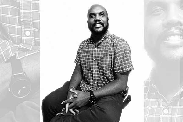 Black and white photo of instructor Rhodri Scantlebury sitting on a stool