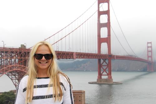 German student Anna Julia poses with sunglasses in front of the Golden Gate bridge