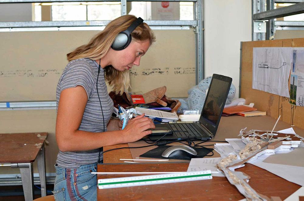 A student listens to music on her headphones while working on a project