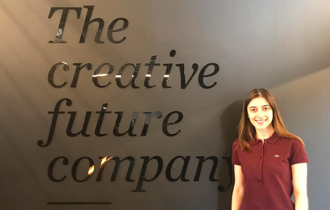 Maria poses in front of a sign at her job at the FutureBrand company