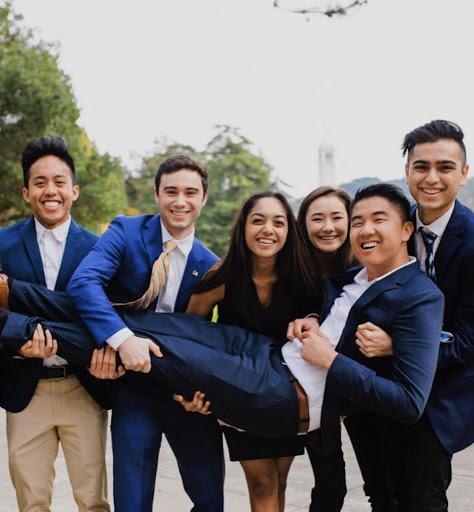 Rafael and his friends post in suits and dresses on the UC Berkeley campus.