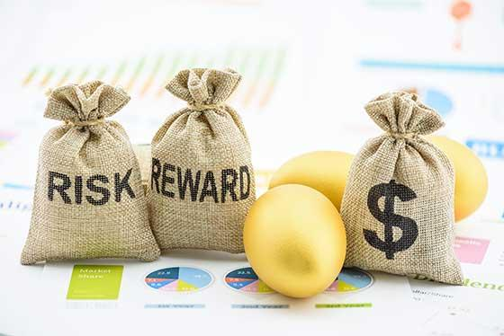 Photo of risk, reward and money bags on top of stock market printouts