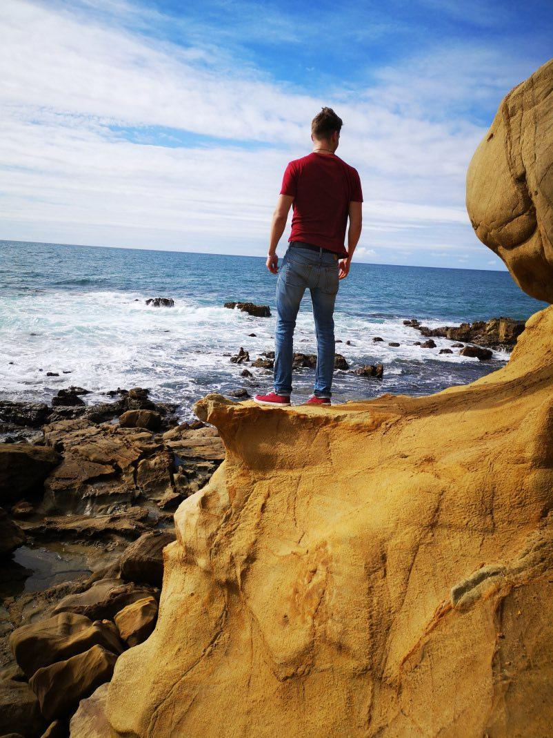Markus standing at the edge of a cliff, with his back turned to face the rocky shore of an ocean.